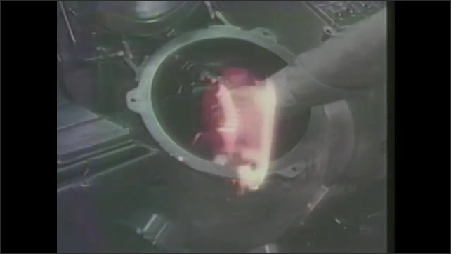1980s: Machine. Man places item inside machine. Fire ignites around coil and ball forms and is released and floats up. Crystals fall in a large group.