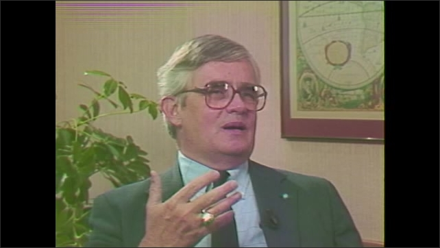 1980s: Crystals form. Man in suit sits in chair talking.
