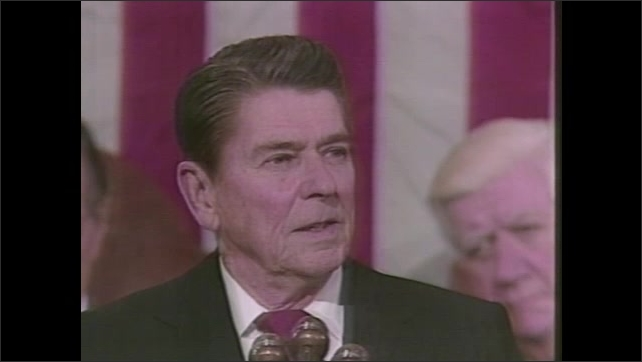 1980s: People stand around plans on drawing table, talking. President Ronald Reagan gives speech. Senate applauds. Space Shuttle launches.