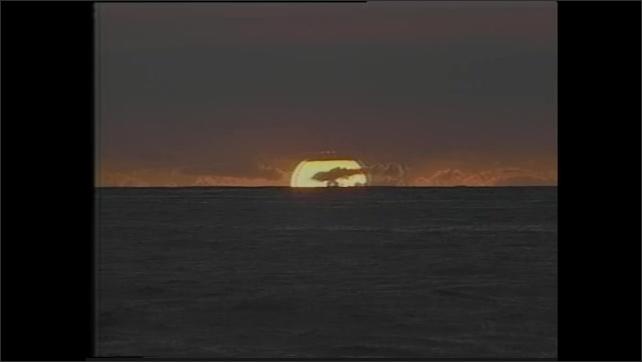 1990s: Sun sets over rolling ocean waves.