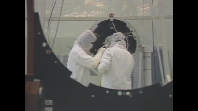 1980s: UNITED STATES: workers in protective clothing inside NASA laboratory. Laser telescope in lab.