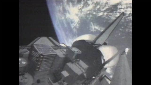 1980s: UNITED STATES: light external tank preparation. Space shuttle in space. View of Earth from space