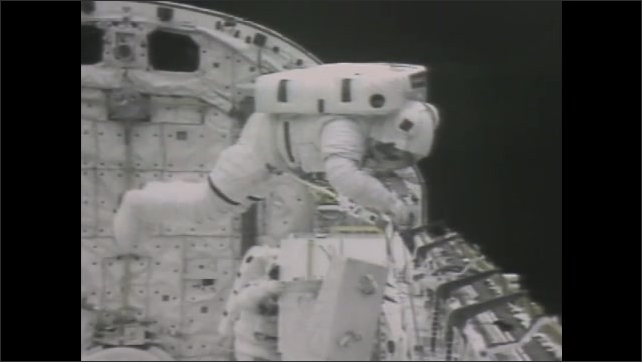 1980s: UNITED STATES: astronauts walk outside shuttle in space. Electrophoresis experiments in space.