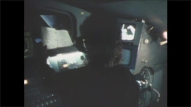 1980s: UNITED STATES: man and lady work on control panels. Astronaut on flight assignment. Male and female astronauts at work