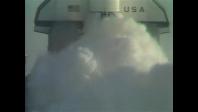 1980s: UNITED STATES: man in space suit. Shuttle prepares for lift off. Test flight. Clouds around shuttle.