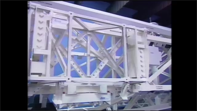 1990s: Men stand next to full size model of space station truss.