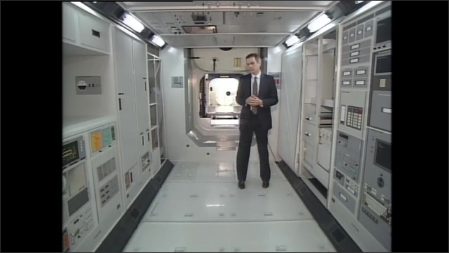 1990s: Man stands inside laboratory module of space station, talks.