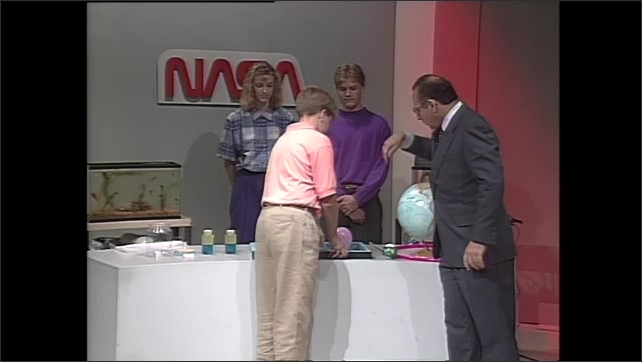 1990s: Man stands by table, talks. Teen boy walks around table, other teens stand behind table and watch. Man and boy hold up wooden frame with balloon attached.