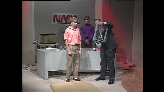 1990s: Man and teen boy stand in front of table, teens stand behind table and watch. Man picks up frame with balloon attached, talks. Man hands frame back to boy.