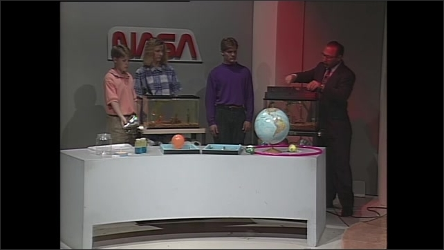 1990s: Man and teens stand behind table. Teens wheel aquarium in front of them. Man stands next to another aquarium, talks.