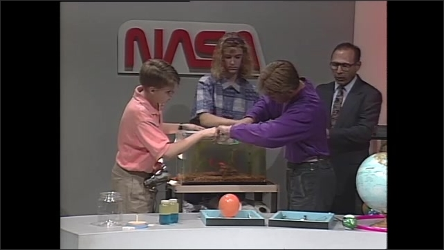 1990s: Man and teens stand behind table, next to aquarium. Teens cover aquarium with film, man talks.