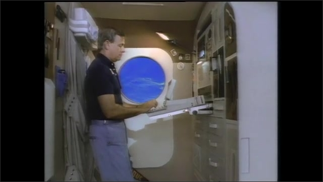 1990s: Man stands inside space station, works on computer. Man floats through space station corridor.