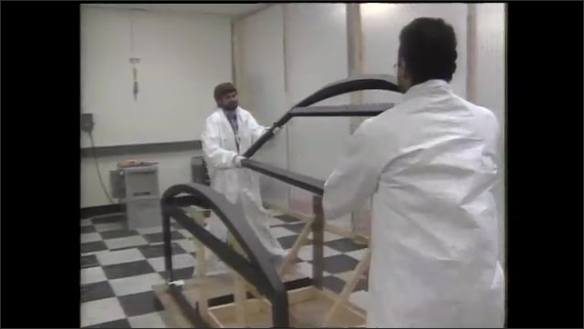 1990s: Men lay plastic film over table. Men assemble materials,