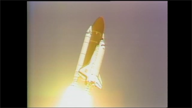 1990s: Long shot, rocket launching. Views of rocket in flight.