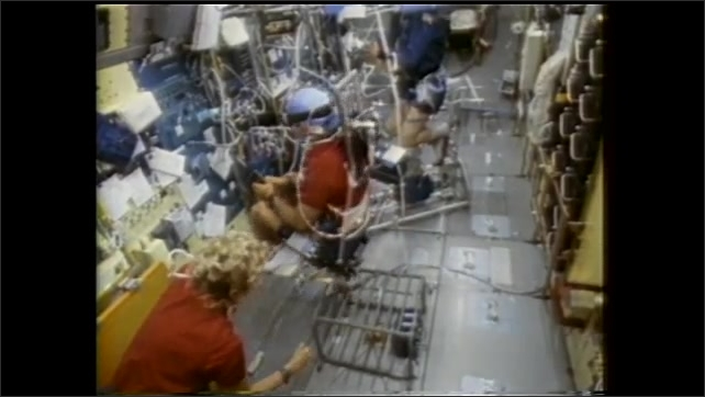 1990s: Men sitting in equipment on spacecraft, woman spins man.