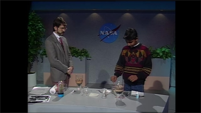 1990s: Man and boy in studio, man sets down beaker of water, boy puts dirt in water. Hand stirs water. Boy picks up water in dropper. Hands drop water into vial.