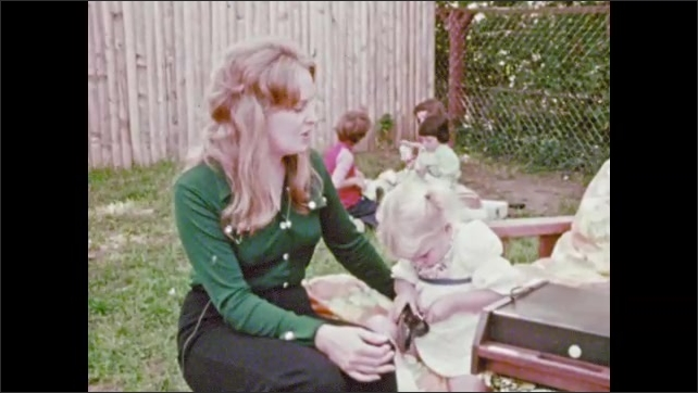 1970s: Woman sitting in yard with girl with parts of medical device on table attached to girl, while talking. Medical device. Girl rides tricycle. Children around kitchen table.