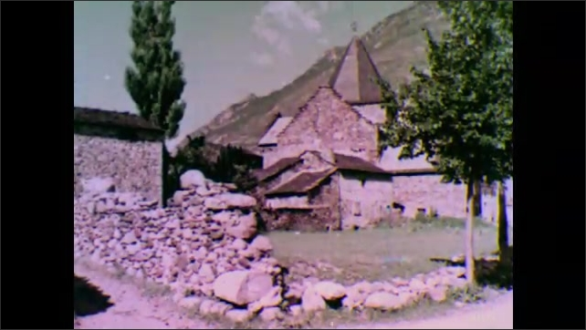 1950s: man takes off backpack and points at town with hiking stick as women and dog sit in field. rustic stone buildings line roads of village in the Spanish Pyrenees of the Catalonia region.