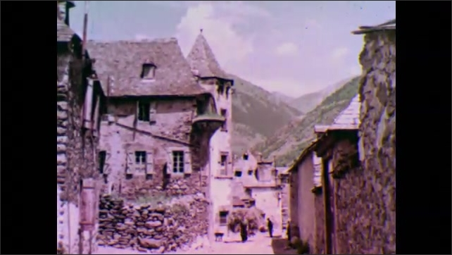 1950s: man with backpack, women and dog walk through rustic town with stone buildings, ramps, porches, balconies and towers in the Spanish Pyrenees of the Catalonia region.