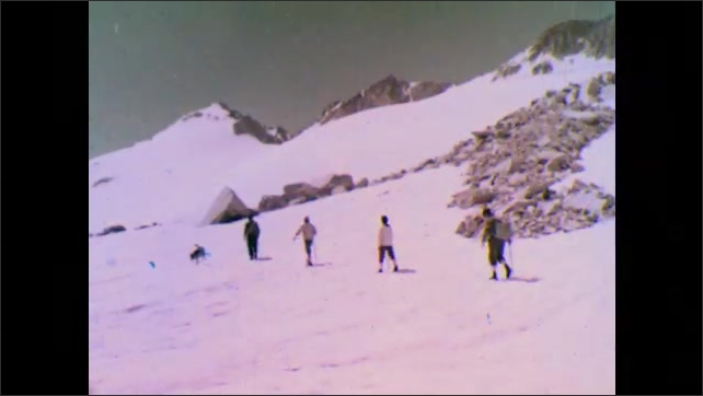 1950s: Mountains.  Hikers and dog walk through snow.