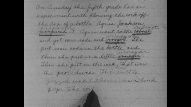 1940s: UNITED STATES: boy sits at desk in classroom. Boy corrects report. Pen writes on paper. Close up of handwriting.
