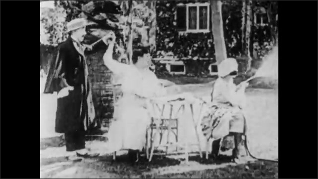 1910s: Man brushes off coat. Girl waters lawn with hose. Man greets seated women on lawn. Girl turns and sprays man with hose. Girl laughs and wipes man off. Man takes girl's arm and walks away.