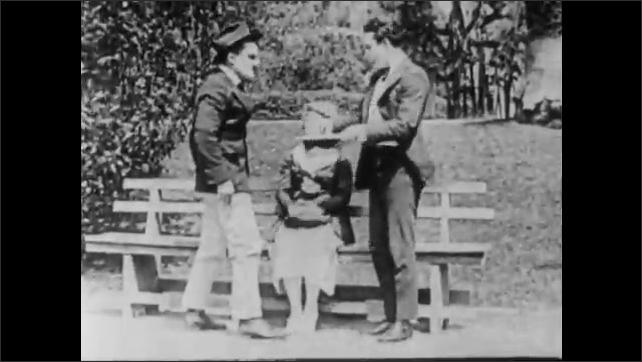 1910s: Man runs around bush. Man jumps onto bench with couple. Man kisses woman. Beau stands and throws punch. Couple on bench tip over. Angry group of people follow man. Angry man trips over man.