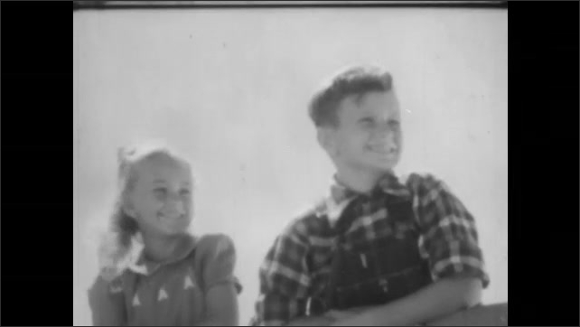 1940s: A boy looks down at a baby rabbit in the grass in a field. A girl stands on a fence in front of a barn. The boy climbs the fence next to her, and she points into the distance.