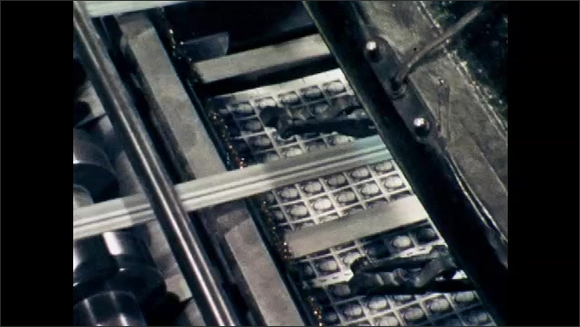 1970s: UNITED STATES: stamp printing press in operation. Stamps on printing press. Machine perforates stamps.