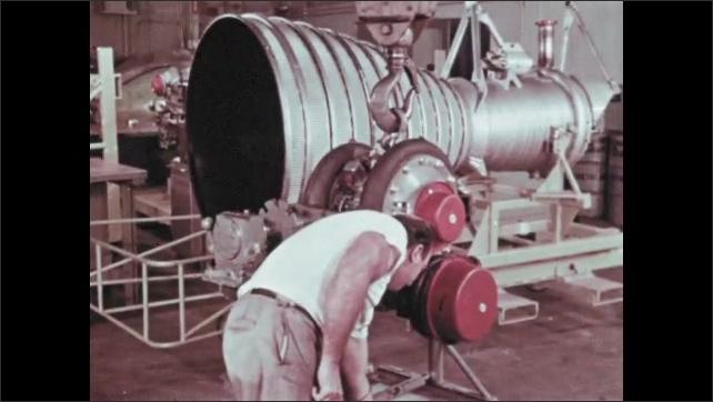 1960s: Machine shop.  Men work on rocket booster.