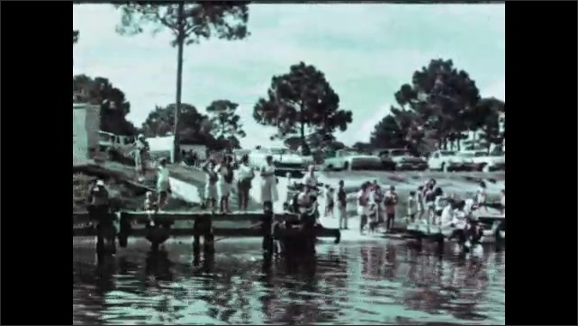1960s: Tug boat in water pulls larger boat carrying rocket equipment. People line long dock along shore, some sitting, some standing.