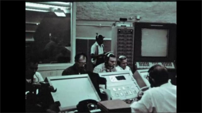 1960s: Men in NASA mission control look at printouts from large printers. Men sit at consoles. Rocket sits on launch pad.