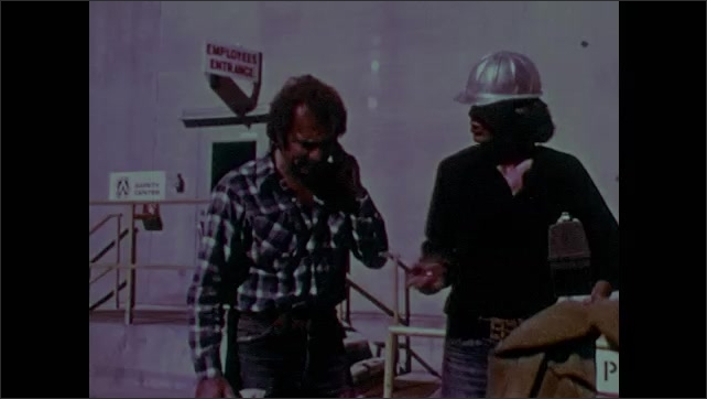 """1980s: Factory building, sign """"employees entrance"""", men leave, man in hardhat talks, removes safety goggles. Man points, they smile, say goodbye. Man gets in car."""