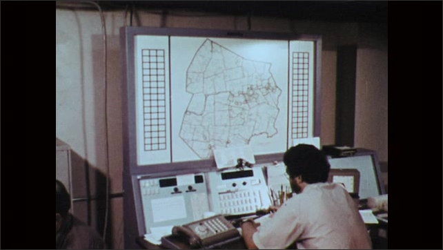 1970s: Civic defense workers in emergency center plan for flood. Workers broadcast on air to evacuate area. Workers unroll map. Men point to rivers on map.