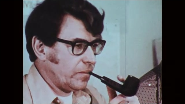 1970s: Group of men talk in office studying a weather report. Man listens and smokes a pipe.