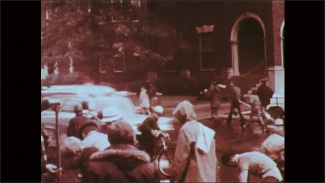 1970s: Woman runs down neighborhood street. Crowd gathers on street corner of city. Car drives by with megaphone. Police and emergency vehicles race down street. Crowds line city streets.
