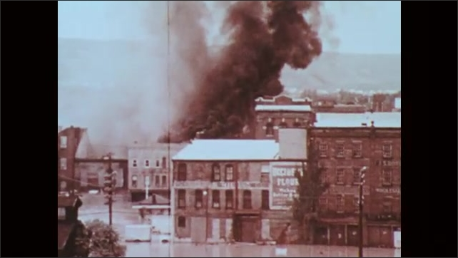 1970s: Firefighters hose down burning building in flooded city. Smoke and flames rise from flooded city. Aerial view of burning buildings in flood zone.