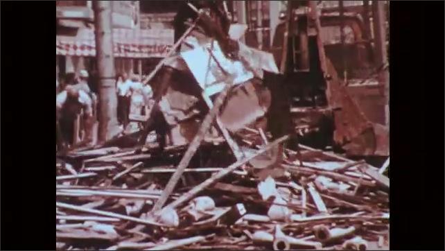 1970s: Bulldozers push trash and debris down flooded city streets. Bulldozers dump debris into dump trucks. Men pressure wash stets. Men shovel and sweep debris from sidewalks.