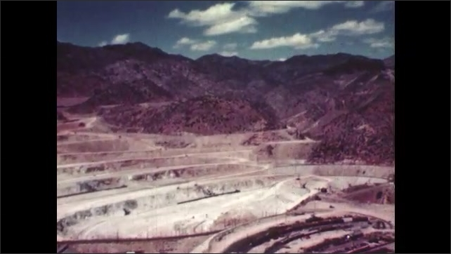 1950s: UNITED STATES: terraces cut into rocks. Mine in mountains. View across copper mine in mountain landscape. Car drives along track in mountains