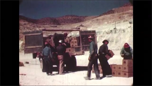 1950s: UNITED STATES: view across copper mine. Drilling hole at mine. Man moves boxes of explosives from safety zone to drilling hole. Man throws box away