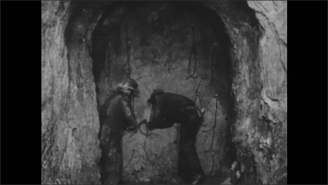 1950s: Two men in hardhats in mine shaft place dynamite into holes in wall of tunnel with poles.