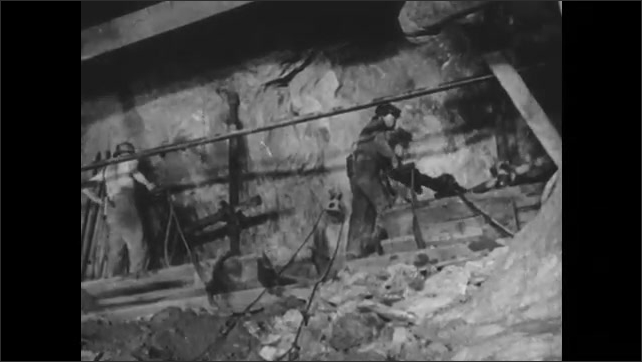 1950s: Two men in mine work using machinery to dig into mine walls. Man uses power tool to drill into mine wall.