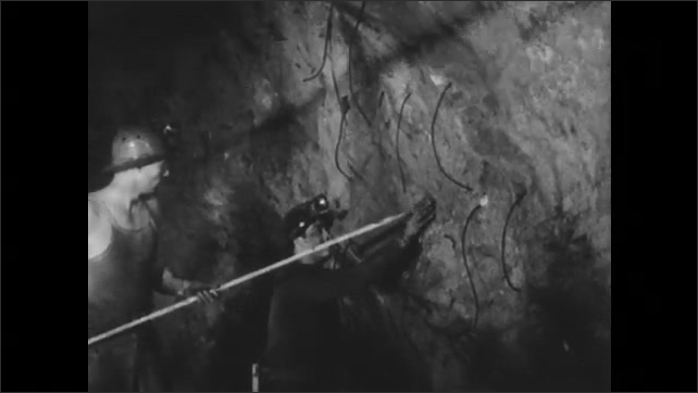1950s: Two men in hardhats in mine shaft place dynamite into holes in wall of tunnel with poles. Man prepares wicks to be lit.
