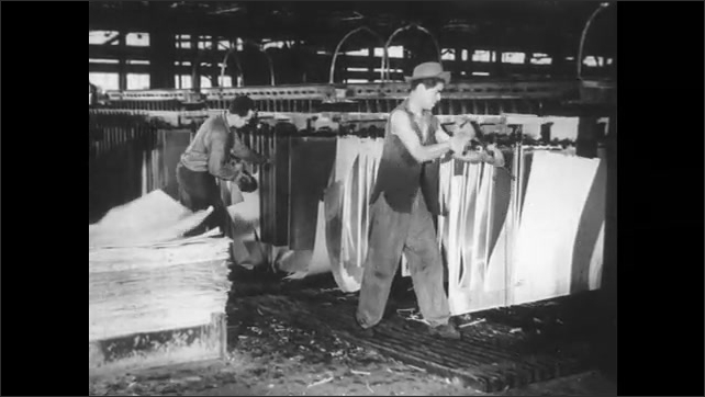 1950s: Two workers secure sheets of metal into a large bin in which they're stored. Men work clearing away thin sheets of copper from sheets of metal. Large crate is lowered onto sheets of metal.