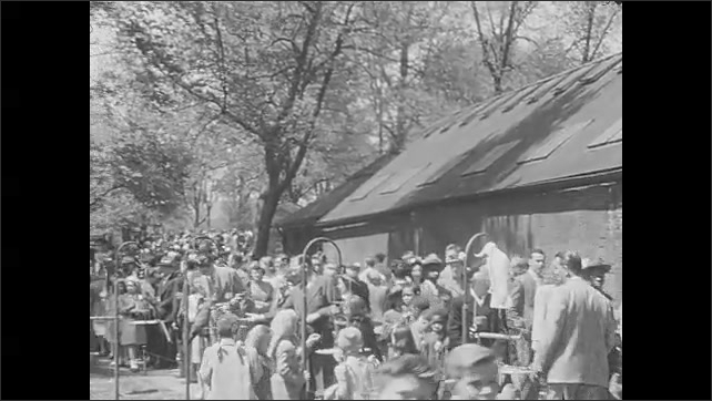 1930s: UNITED STATES: monkeys in enclosure. Crowds gather around birds at zoo