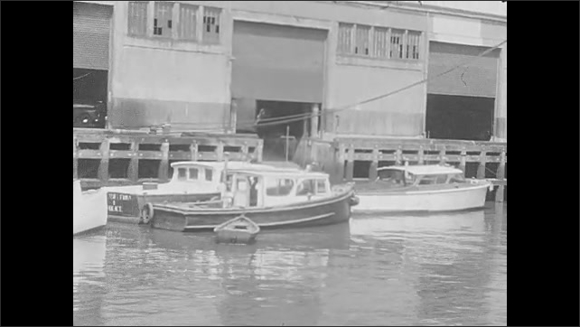 1930s: UNITED STATES: boats on water in dock. Buildings by dock. Ship in harbour