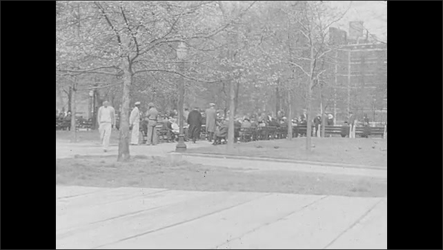 1930s: UNITED STATES: people in park. People sit on park benches