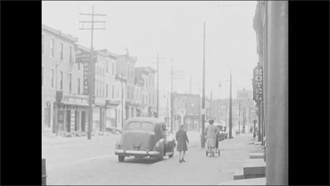 1930s: UNITED STATES: lady walks along street. Car on street. Lady pushes pram along road. Hotel sign