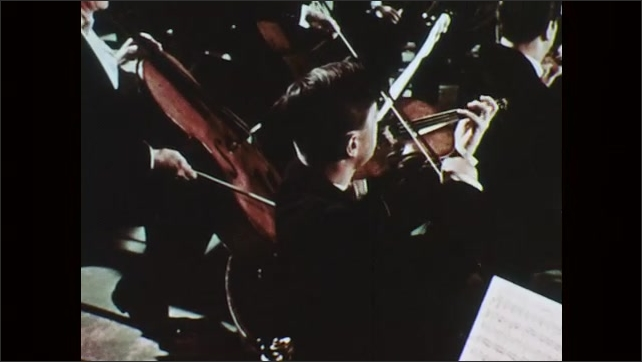 1950s: Violinists place combs onto strings to change tone, players play.
