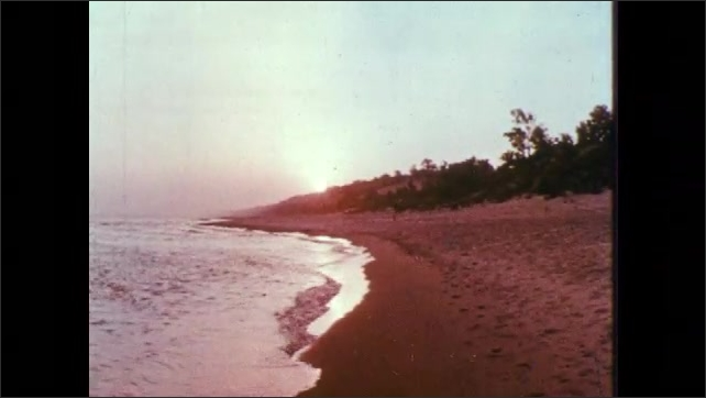 1960s: Seagrass. Water laps against beach.